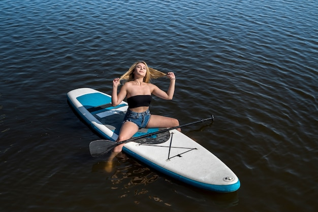 Junge attraktive frau, die auf paddelbrett aufwirft und im heißen heißen sonnigen sommertag entspannt
