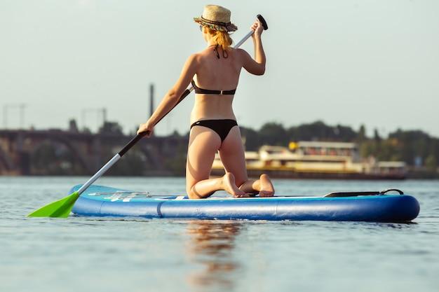 Junge attraktive frau, die auf paddelbrett sitzt