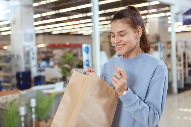 Junge attraktive frau, die aufgeregt schaut und ihre einkaufstasche öffnet. glücklicher weiblicher kunde, der in ihre einkaufstasche schaut