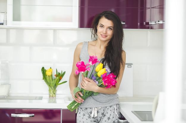 Junge attraktive frau, die blumen hält. dame in der küche mit tulpen. hausfrau morgens, die auf der hauptküche steht.