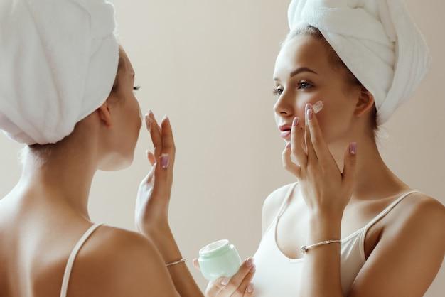 Junge attraktive frau, die creme auf ihr gesicht anwendet, während sie ihr spiegelbild im spiegel betrachtet.