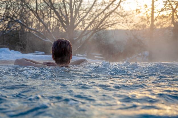 Junge attraktive frau, die draußen wellness mit sauna und swimmingpool im winter genießt