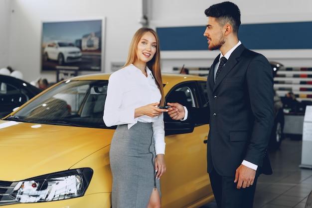 Junge attraktive frau, die ein neues auto im autosalon nah oben kauft