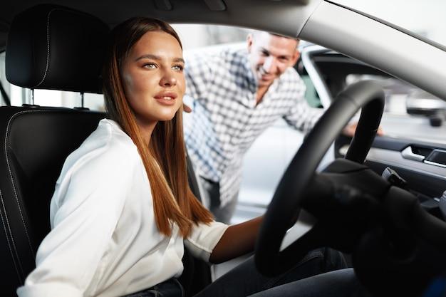 Junge attraktive frau, die ein neues auto in einem autoausstellungsraum sucht
