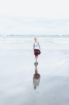 Junge attraktive frau, die entlang des ozeanufers auf einem sandigen strand geht