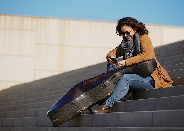 Junge attraktive frau, die ihren smartphone mit musikinstrument verwendet