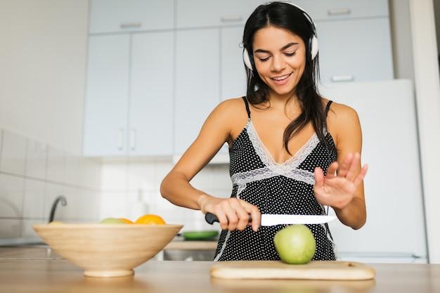 Junge attraktive frau, die in der küche am morgen kocht, obstsalat macht, apfel mit messer schneidet, lächelt, fröhliche stimmung, positive hausfrau, gesunder lebensstil, musik über kopfhörer hört,