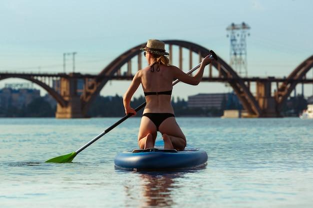Junge attraktive frau, die neben paddle board steht