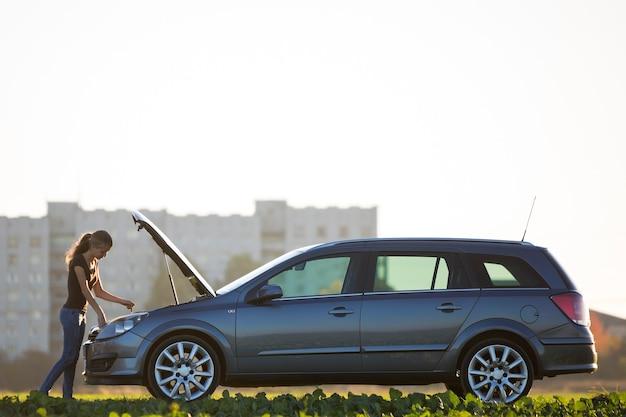 Junge attraktive frau, die ölstand im motor eines autos mit geknallter motorhaube unter verwendung des ölmessstabes auf kopienraum des klaren himmels prüft. transport, fahrzeugprobleme und pannenkonzept.