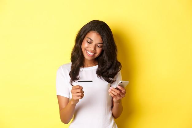 Junge attraktive frau, die online unter verwendung des mobiltelefons mit kreditkarte einkauft und lächelt