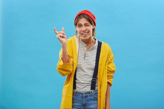 Junge attraktive frau, die roten hut, gelbe jacke und jeansoverall trägt, zeigt etwas sehr wenig mit den händen beim gestikulieren. fischerin, die die größe des fisches demonstriert