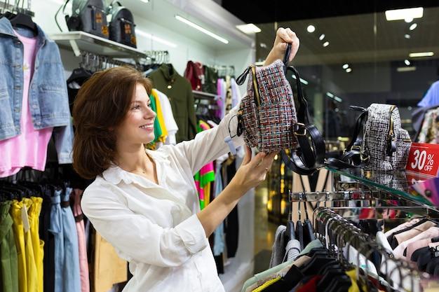 Junge attraktive frau, die rucksack in ihren händen in der gebrauchtkleidung hält und kaufen ausstattet