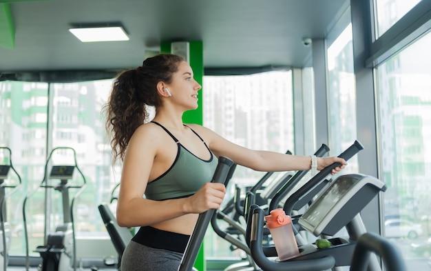 Junge attraktive frau, die sich auf einem elliptischen übungsgerät im fitnessstudio aufwärmt. fitness, gesunder lebensstil konzept.