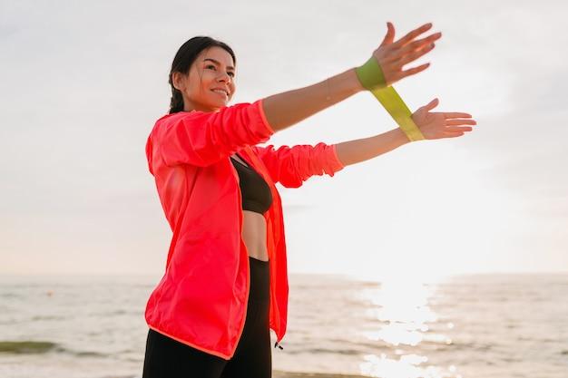 Junge attraktive frau, die sportübungen im morgensonnenaufgang am meeresstrand, gesunden lebensstil tut, musik auf kopfhörern hörend, rosa windbreakerjacke tragend macht, das dehnen im gummiband macht