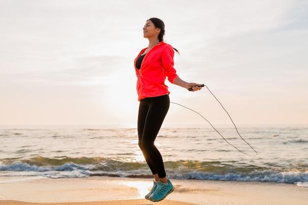Junge attraktive frau, die sportübungen im morgensonnenaufgang am meeresstrand in der sportkleidung, im gesunden lebensstil, im musikhören auf kopfhörern, im tragen der rosa windjackejacke, springend im springseil tut
