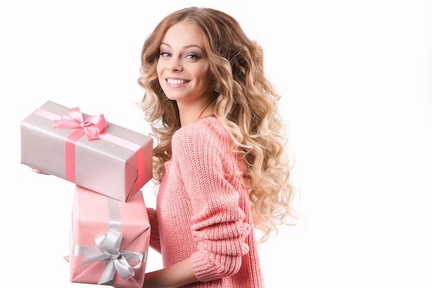 Junge attraktive frau, die stapel bunte geschenkboxen, auf weißem hintergrund hält.