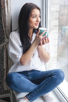 Junge attraktive frau, die tee oder kaffee an ihrer küche trinkt. dame indors entspannung mit tasse heißem getränk