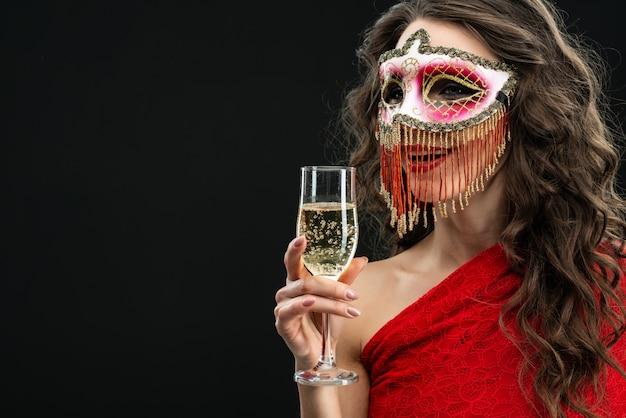 Junge attraktive frau, die venetianische karnevalsmaske gegen schwarzen hintergrund trägt