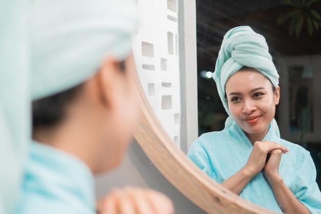 Junge attraktive frau, die vor spiegel mit handtuch am badezimmer steht