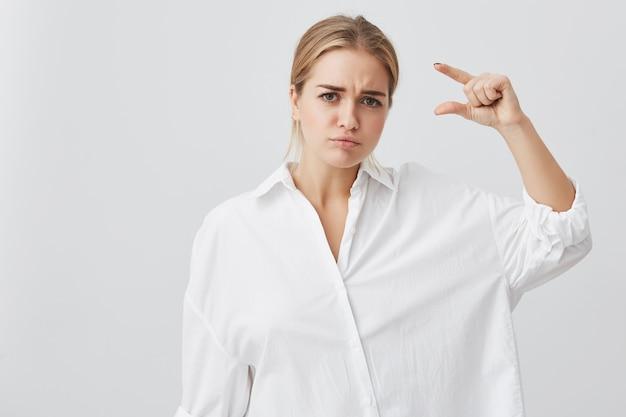 Junge attraktive frau, die weißes hemd trägt, das etwas sehr wenig mit den händen beim gestikulieren zeigt. blonde studentin, die größe von etwas demonstriert