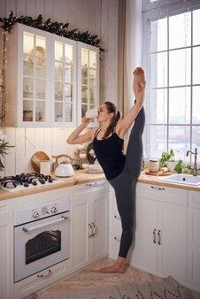 Junge attraktive frau, die yoga an der modernen küche praktiziert