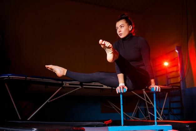 Junge attraktive frau, die yoga praktiziert, in der hand-balance-übung, handstand, training, in sportbekleidung, schwarzen leggings und top, drinnen in vollem wachstum steht