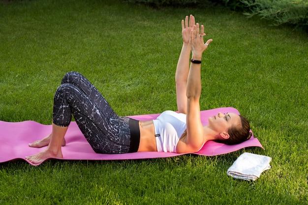 Junge attraktive frau, die yoga praktiziert, liegestütze, liegestütze macht. sie trainiert im freien