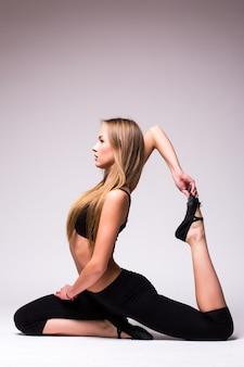 Junge attraktive frau, die yoga tragend trägt schwarze sportbekleidung, kühle stadtart, volle länge, graue wand, seitenansicht