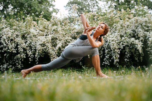 Junge attraktive frau führt übungen mit ihrem eigenen gewichtsgrün in der park-yoga-pose zum dehnen durch