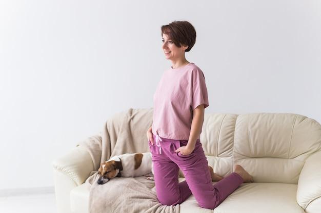 Junge attraktive frau gekleidet im schönen bunten pyjama, der mit hund als modell in ihrem leben aufwirft