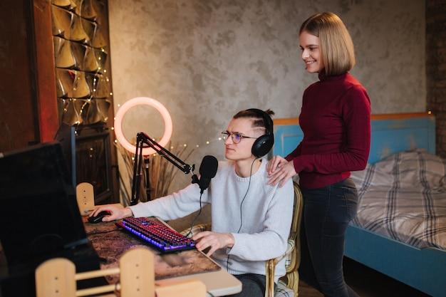 Junge attraktive frau helfen ehemann, gutaussehender mann zu arbeiten, sitzt am tisch und arbeitet am computermann