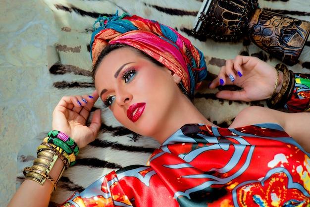 Junge attraktive frau im afrikanischen stil mit trommel auf fell