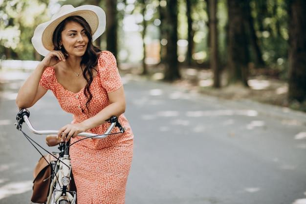 Junge attraktive frau im kleid, das fahrrad reitet