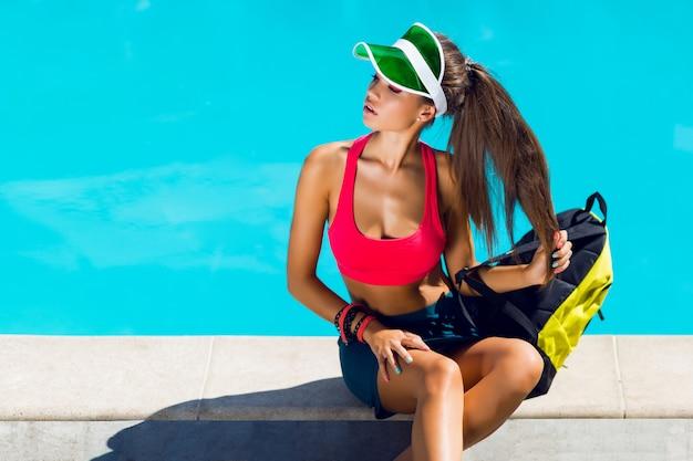 Junge attraktive frau im stilvollen sportoutfit, das nahe pool am heißen sommertag sitzt. haben sie einen perfekt gebräunten, schlanken körper.