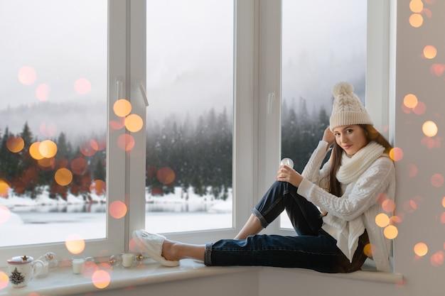 Junge attraktive frau im stilvollen weißen strickpullover, im schal und in der mütze, die zu hause auf der fensterbank zu weihnachten sitzen und glasschneekugelgeschenkdekoration, winterwaldansicht, lichter bokeh halten