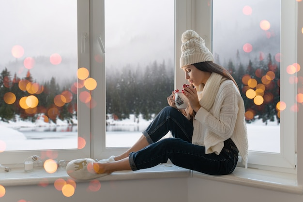 Junge attraktive frau im stilvollen weißen strickpullover, im schal und in der mütze, die zu hause auf fensterbank an weihnachten halten tasse halten, die heißen tee trinkt, winterwaldhintergrundansicht, lichter bokeh