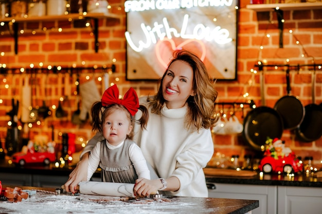 Junge attraktive frau im weißen winterpullover und im kleinen kleinkindbabymädchen im kleid und in der roten schleife, die kekse in der küche machen.