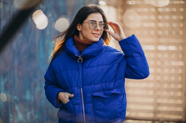 Junge attraktive frau in der blauen winterjacke