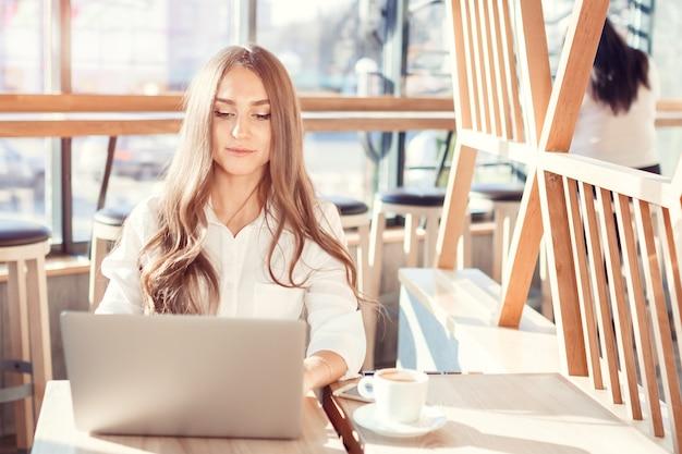 Junge attraktive frau in der bluse, die am computer arbeitet. ein schönes mädchen an einem hellen sonnigen tag sitzt am kostüm in einem café