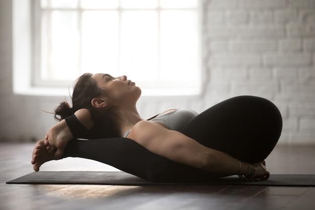Junge attraktive frau in der jogischen schlafhaltung