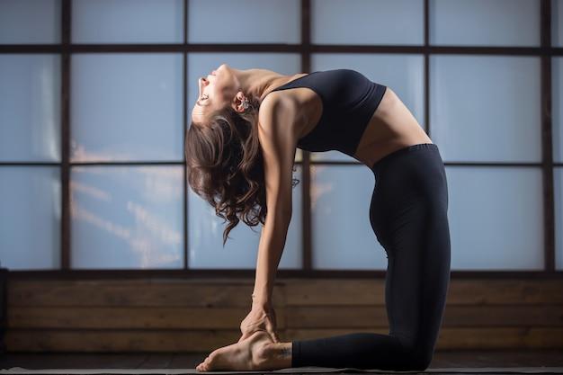 Junge attraktive frau in der ustrasana-pose, studio-abend pra