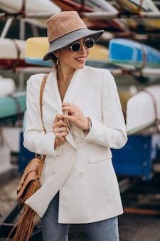 Junge attraktive frau in der weißen jacke, die draußen geht Kostenlose Fotos