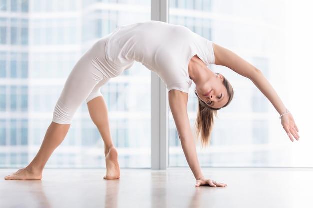 Junge attraktive frau in der yogahaltung