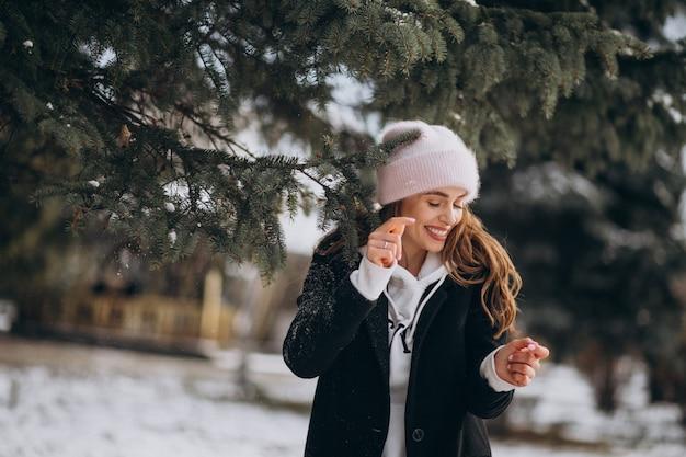 Junge attraktive frau in einem winterpark in einem netten hut