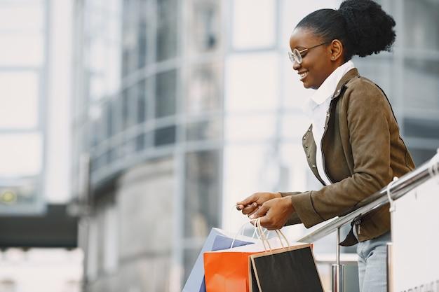 Junge attraktive frau in jacke und hält viele einkaufspakete und geht die straße entlang. shopping-konzept