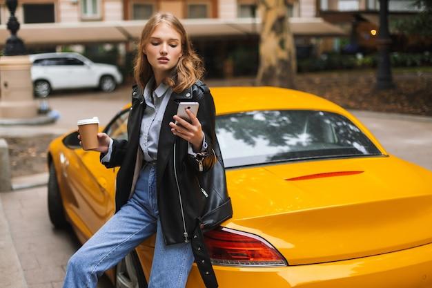 Junge attraktive frau in lederjacke, die sich auf gelben sportwagen stützt, der tasse kaffee hält, um in hand zu gehen, während nachdenklich handy auf stadtstraße verwendet