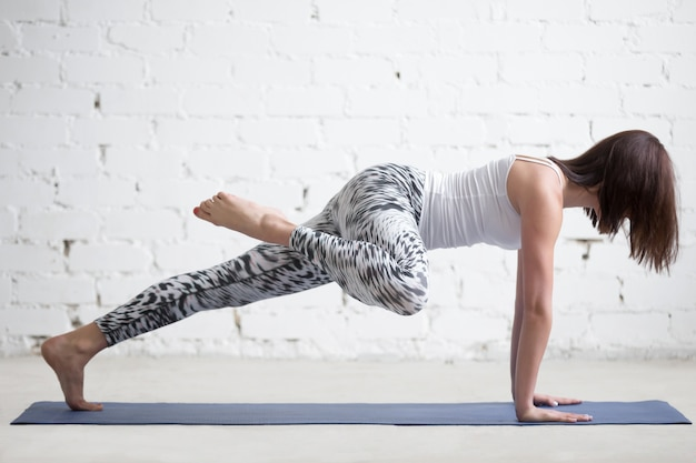 Junge attraktive frau in plank pose, variation, weißes studio
