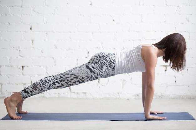 Junge attraktive frau in plank pose, weißes studio