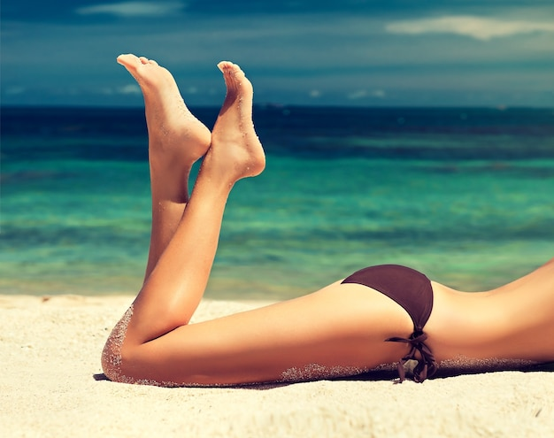 Junge, attraktive frau liegt am strand