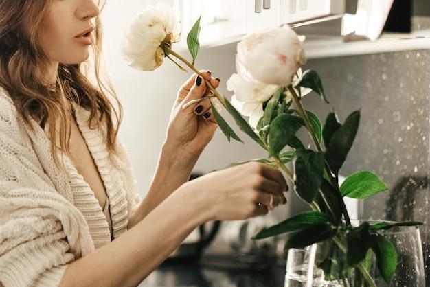 Junge attraktive frau macht einen strauß weißer pfingstrosen in einer vase
